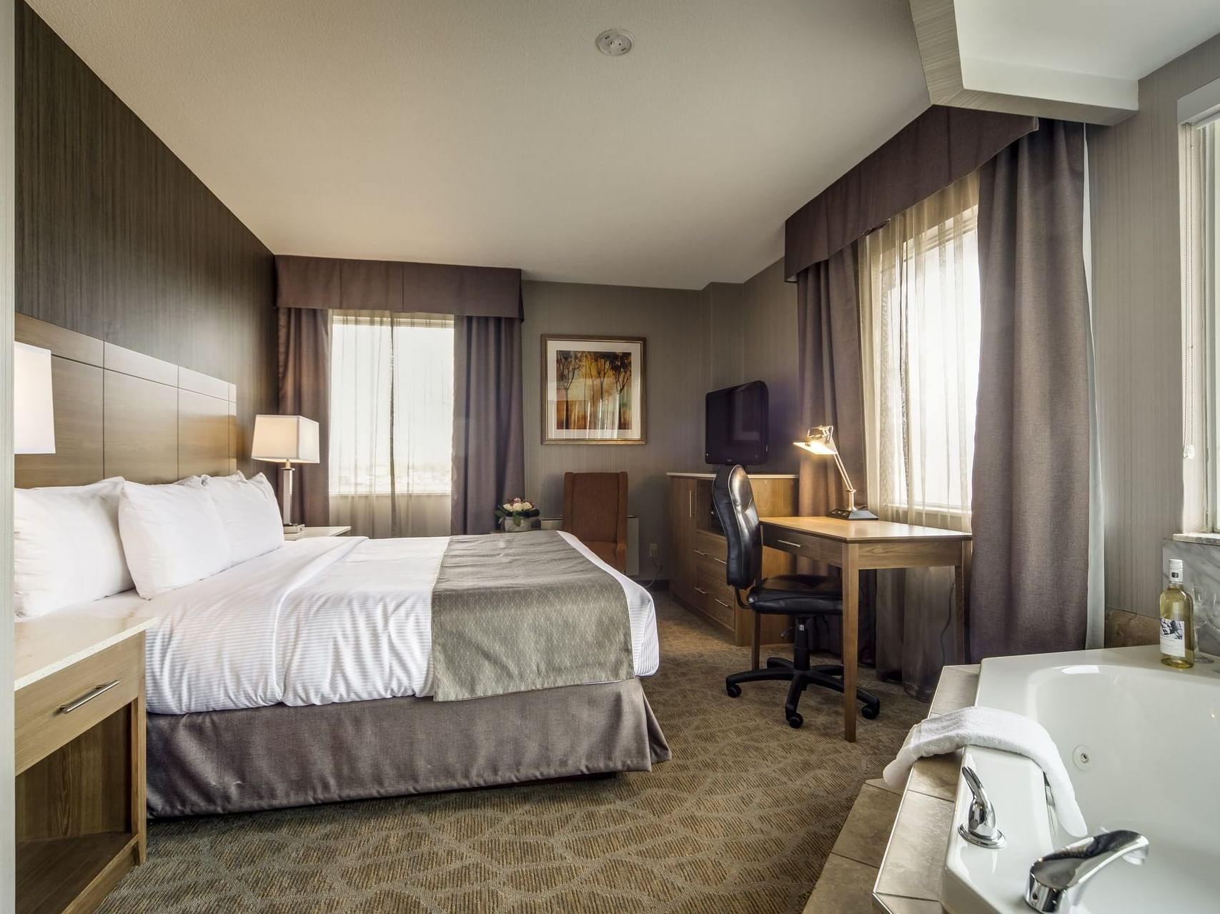 Double bed, Jacuzzi, working table and chair - Monte Carlo Inn Airport Suites
