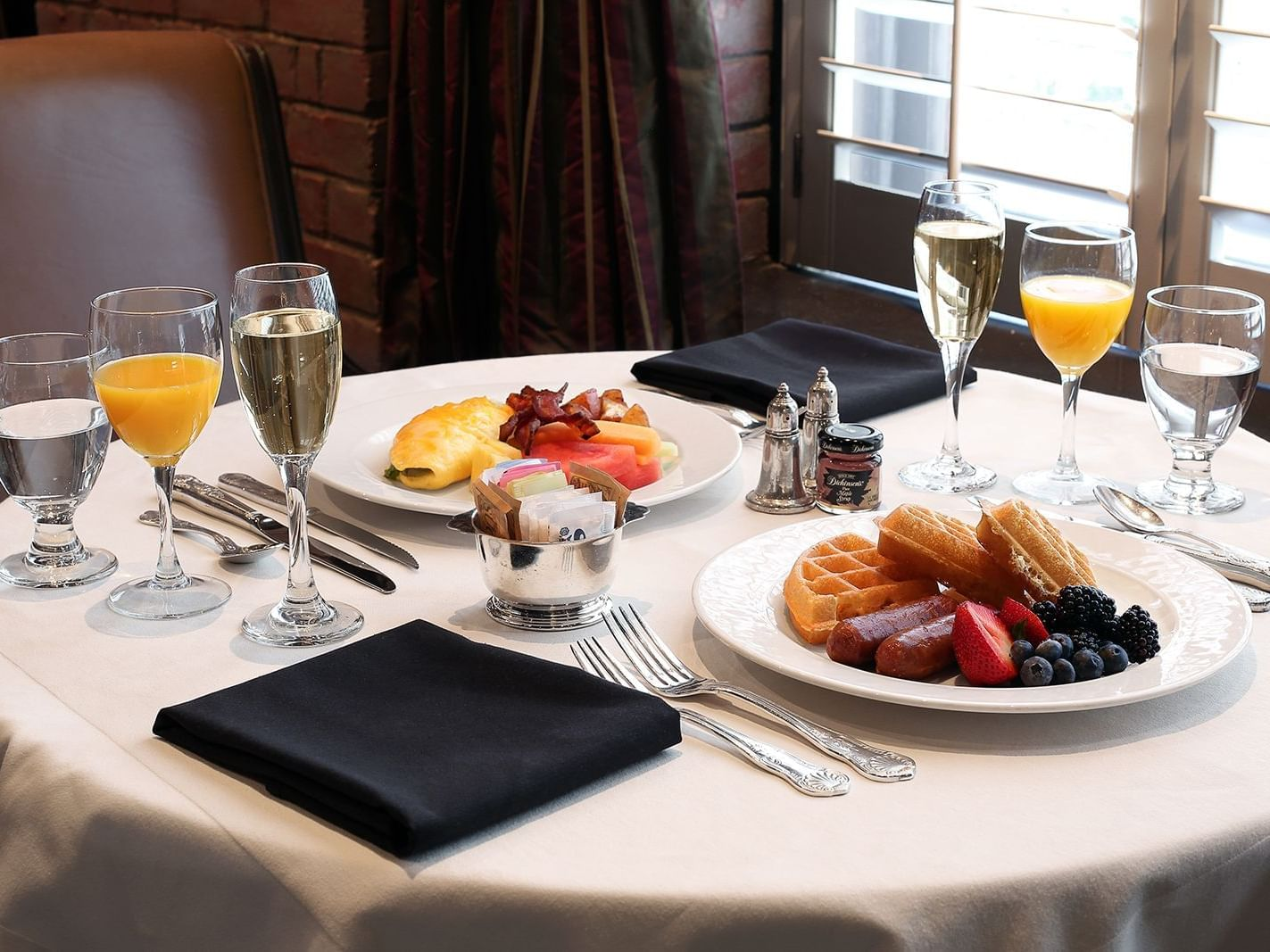 table with two breakfast plates, with champagne and orange juice