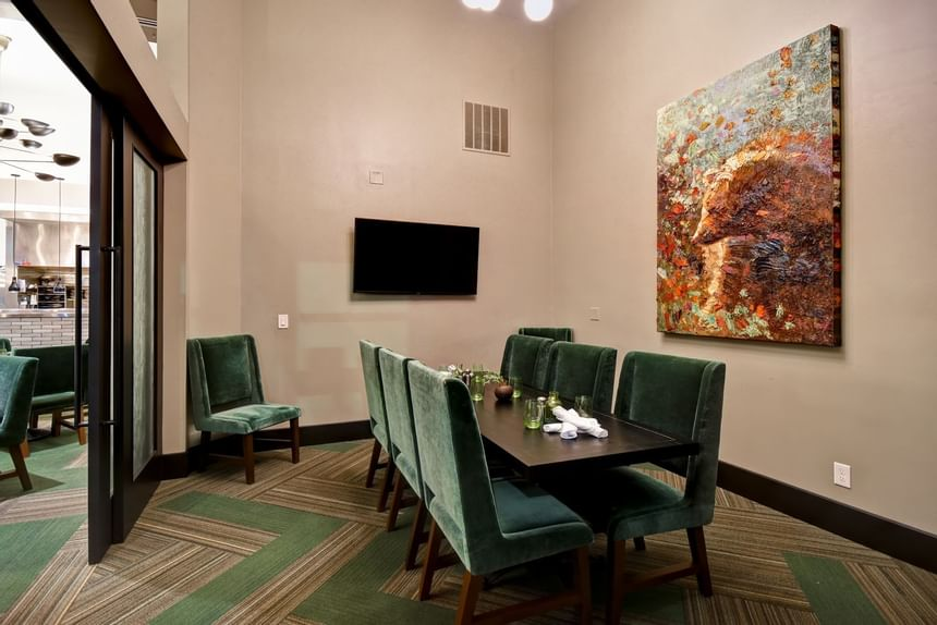 a painting hanging over a public dining table