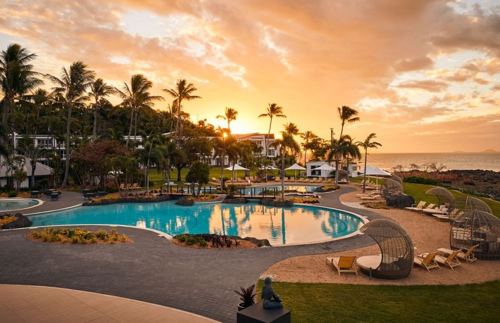 Pool with sun loungers at sunset at Daydream Island Resort