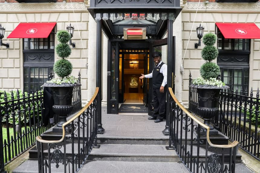 Welcome to The Eliot Hotel! A doorman smiling and gesturing in welcome to the open door to the hotel.