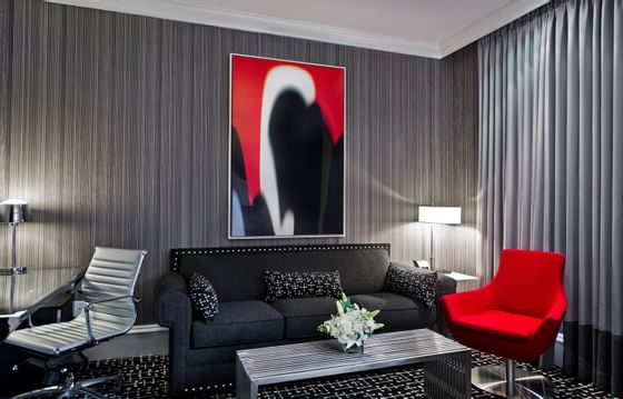 a black couch and red chair in a hotel room