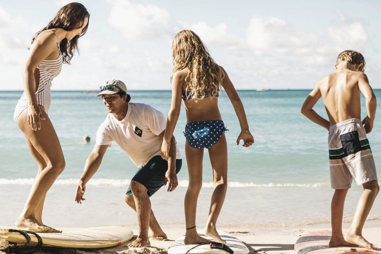 kids on beach taking surf lesson