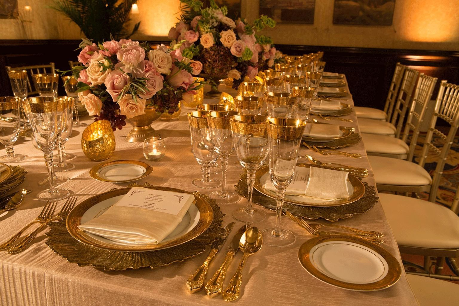 table decorated with gold place settings and roses