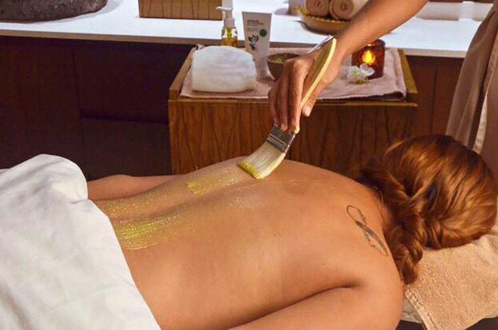 A woman having body treatments in Okom spa at The Reef 28