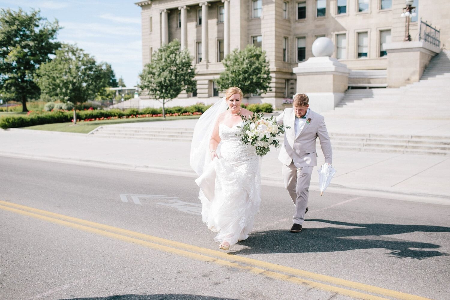 a bride and groom walking across a street
