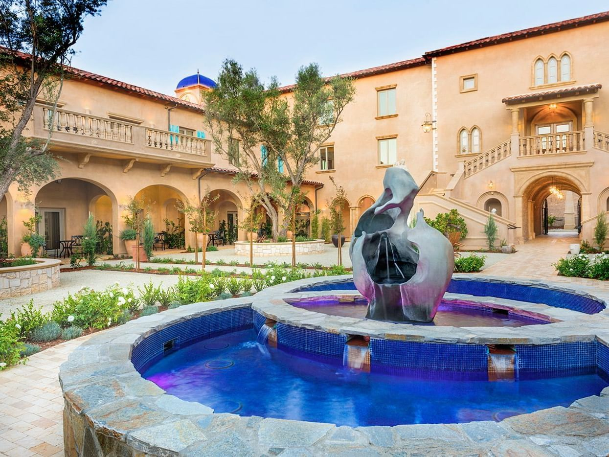 Fountain in courtyard with exterior view of hotel in back