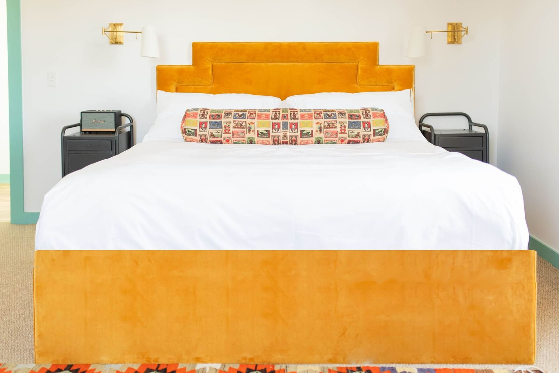 bed with orange bedframe in white room