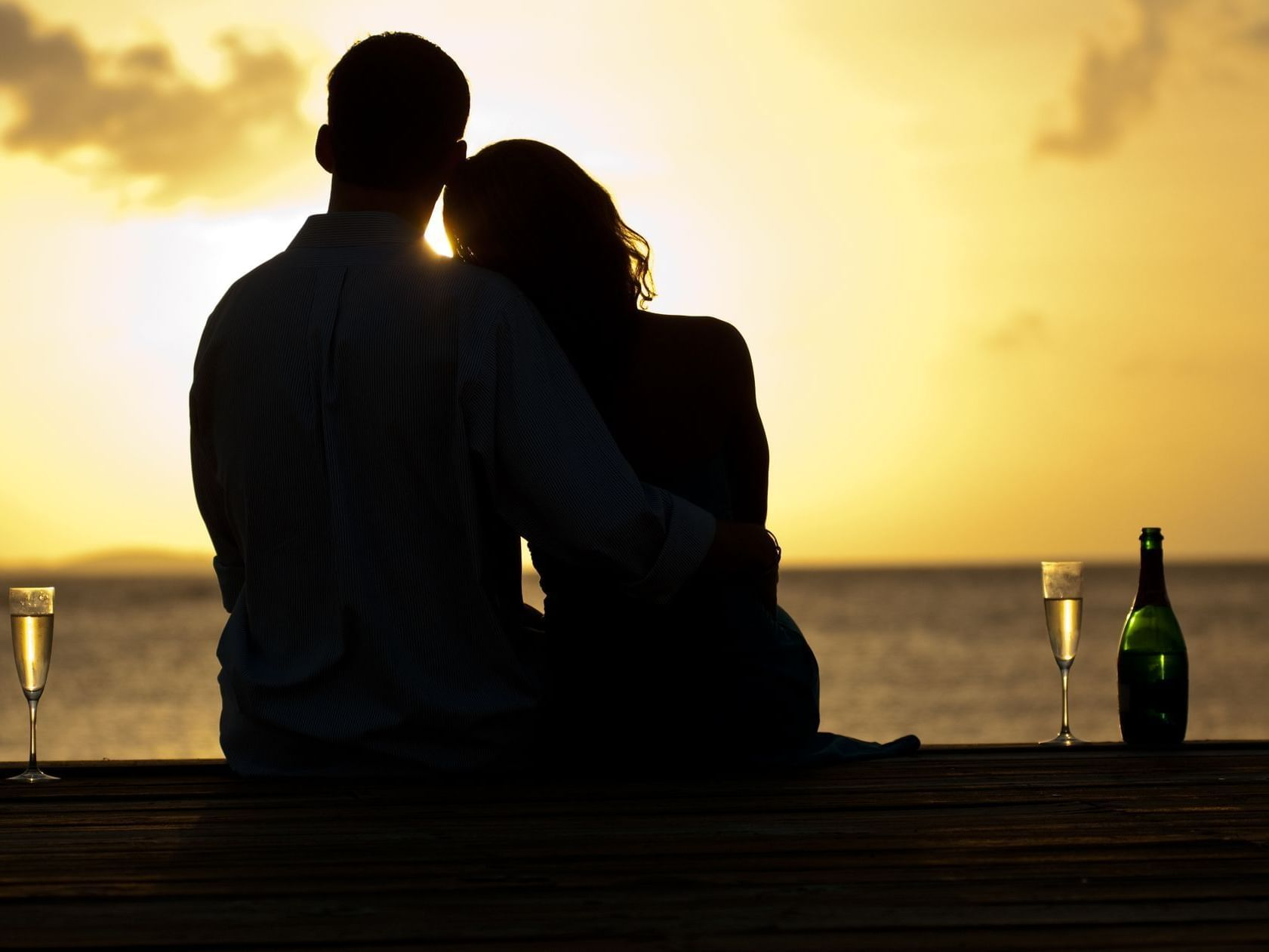 Couple sitting in sand at sunset