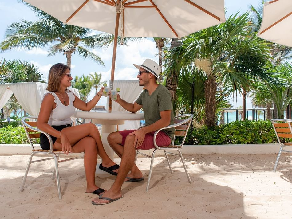 A couple having a drink at Deli snack bar at The Reef Playacar