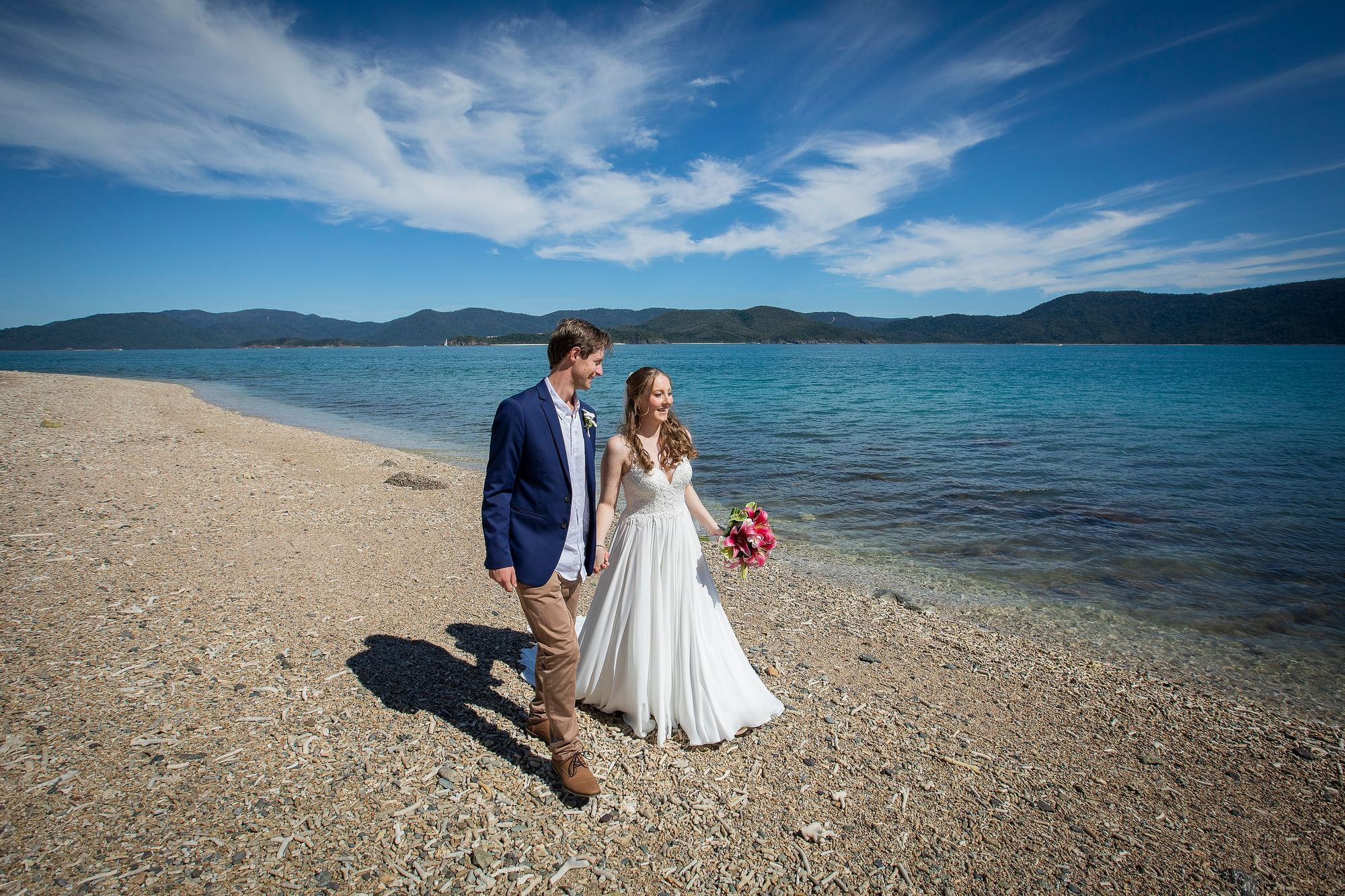 Wedded couple walking on beach at Daydream Island Resort
