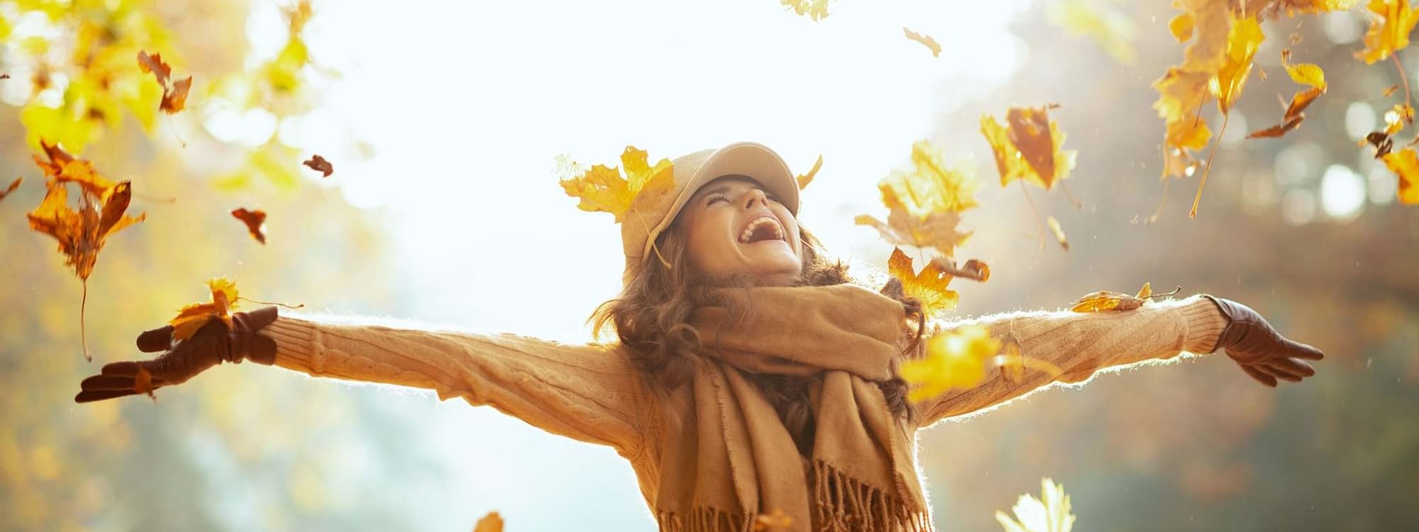 Woman catching falling yellow leaves