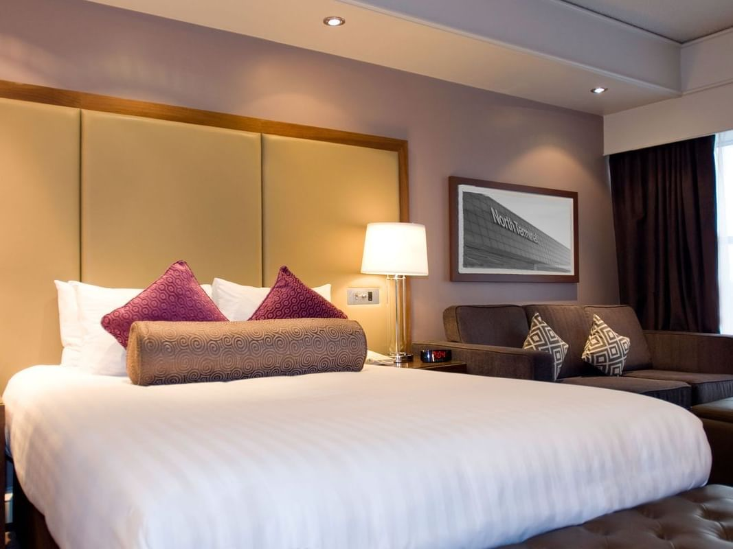 The King Room at Sandman Signature London Gatwick Hotel with one king bed (with premium pillow-top) and a 3 seater sofa on the side of the bed next to the window