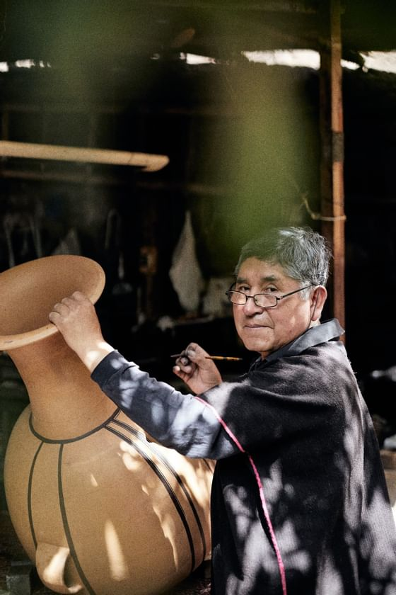 A person painting a huge clay pot  near Hotel Sumaq
