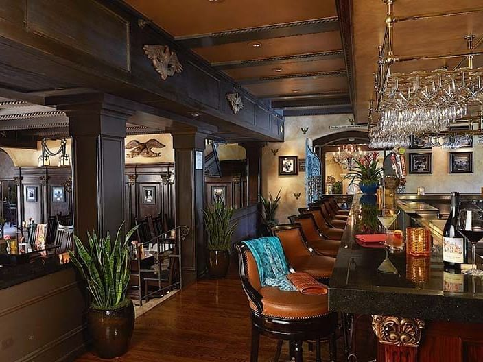 bar with leather barstools and view to dining room