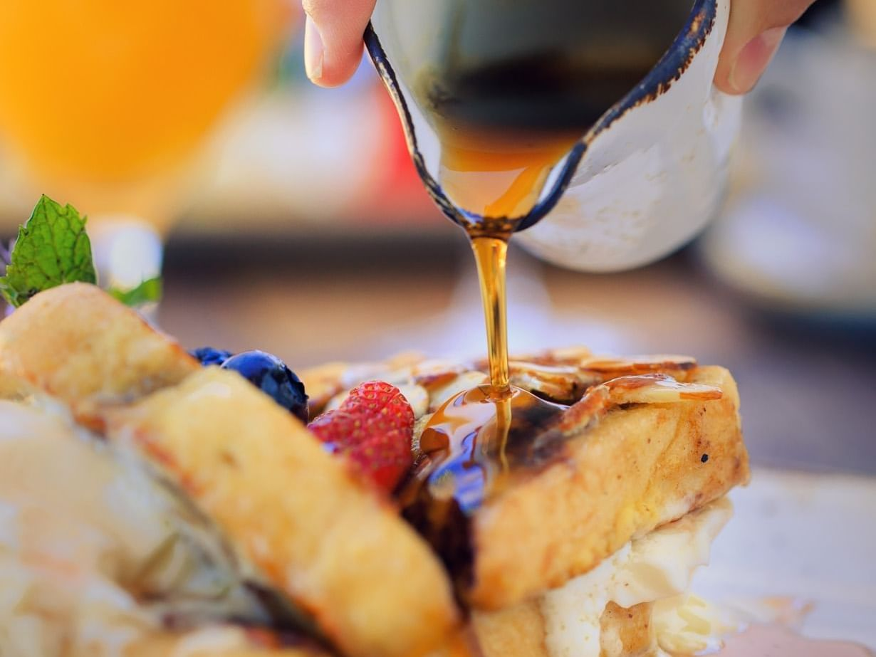 Syrup being poured over french toast