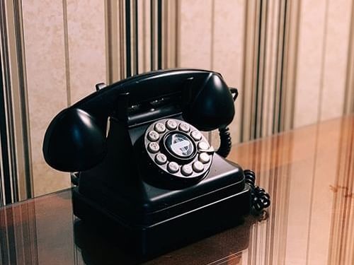A vintage telephone on wooden surface at Heritage House Resort
