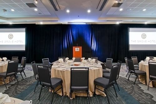 two screens facing tables and chairs in a ballroom