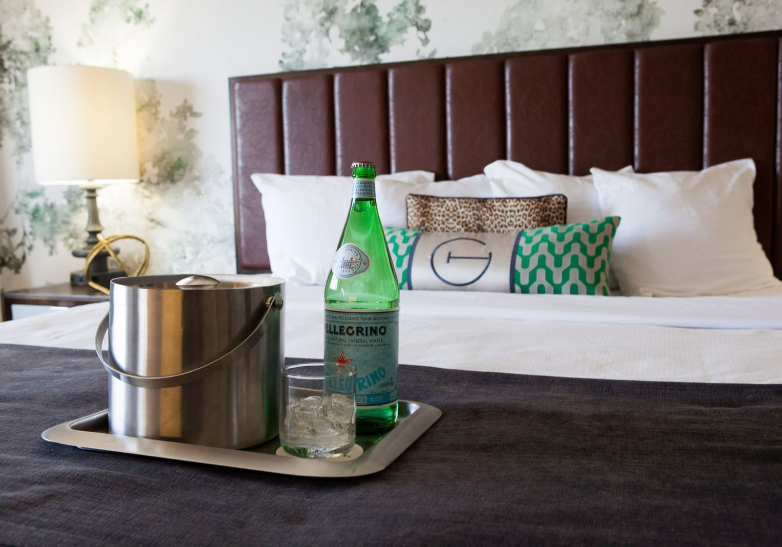 a bottle of sparkling water on a hotel bed