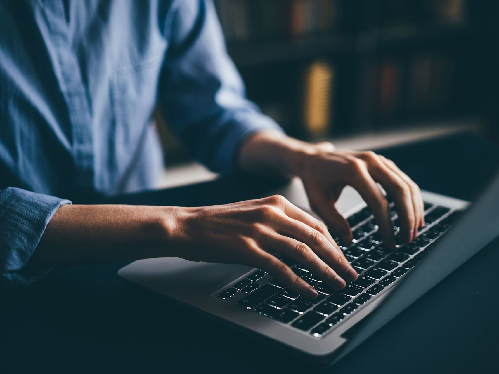 Close up on a person typing on a keyboard at Henn Na Hotel