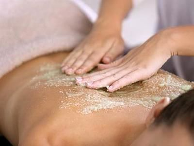 woman having back exfoliation treatment in spa at Amora Hotel