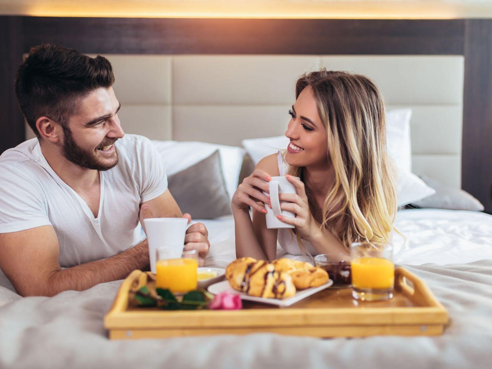 Couples having breakfast in bed