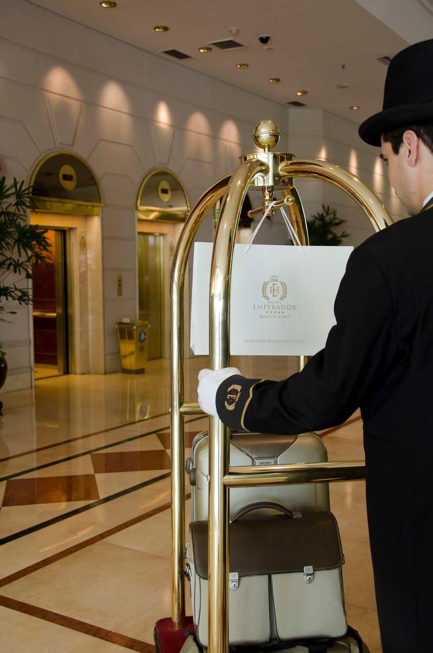 Concierge pushing a luggage cart at Hotel Emperador