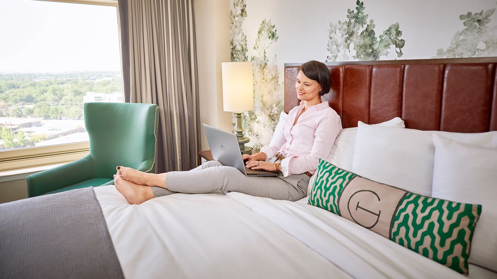 a woman sitting on a bed using a laptop