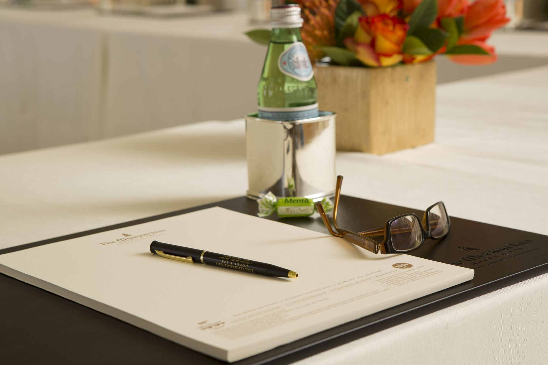 notepad with glasses and water bottle