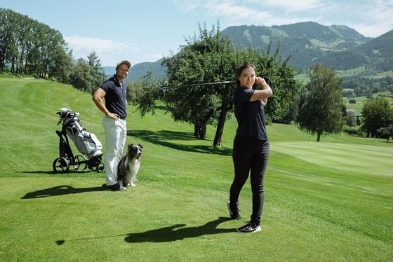 Paar mit Hund am 18 Loch Golfplatz von Schloss Pichlarn