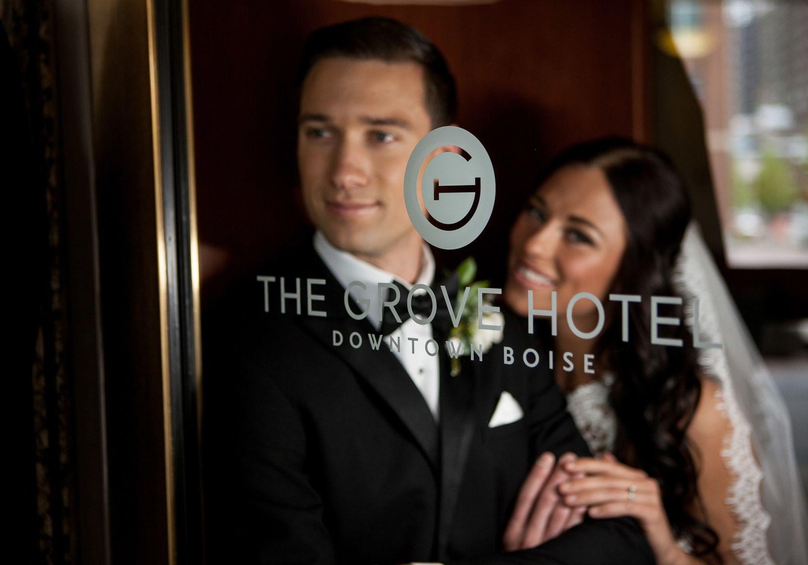 a bride and groom behind a glass door