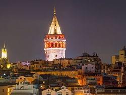 Exterior view of Galata Tower at night near CVK Hotels