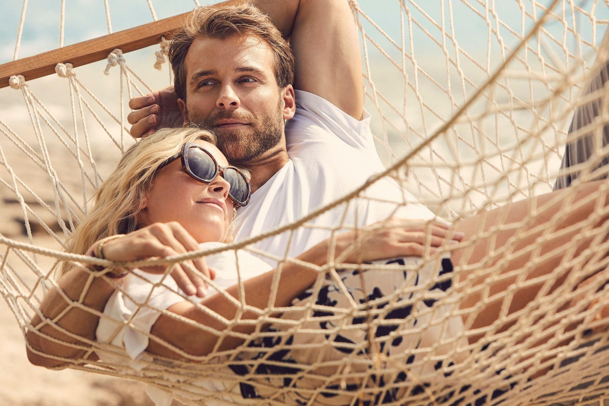 Couple sun bathing on hammock at Daydream Island Resort