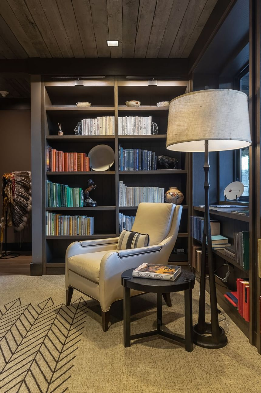 A chair near a book shelf in the Library at Hotel Jackson
