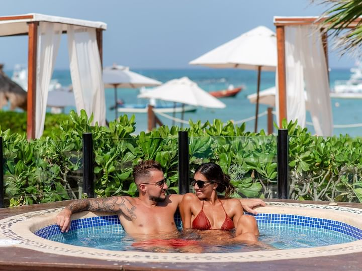 Couple spending time in outdoor jacuzzi at The Reef Coco Beach