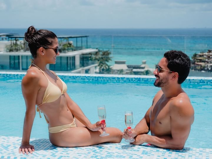 A couple having a drink in pool at The Reef Resorts