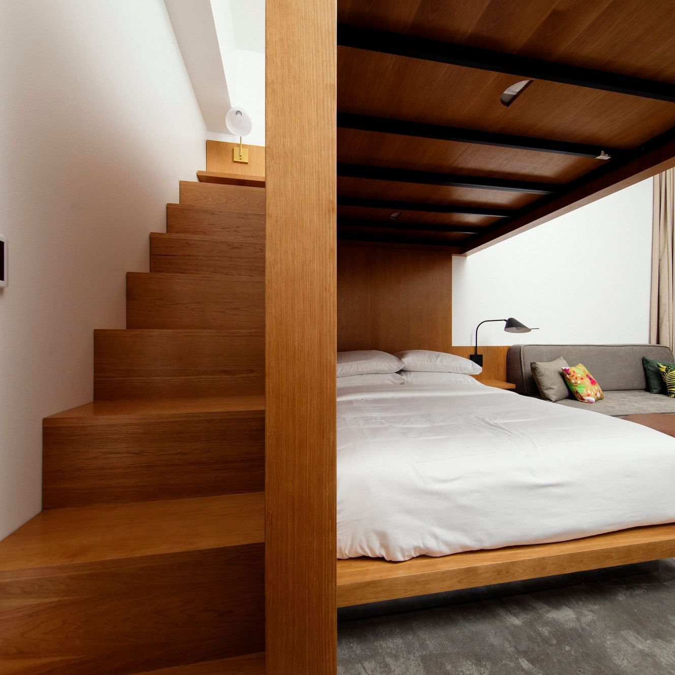 room with loft-style bed and staircase