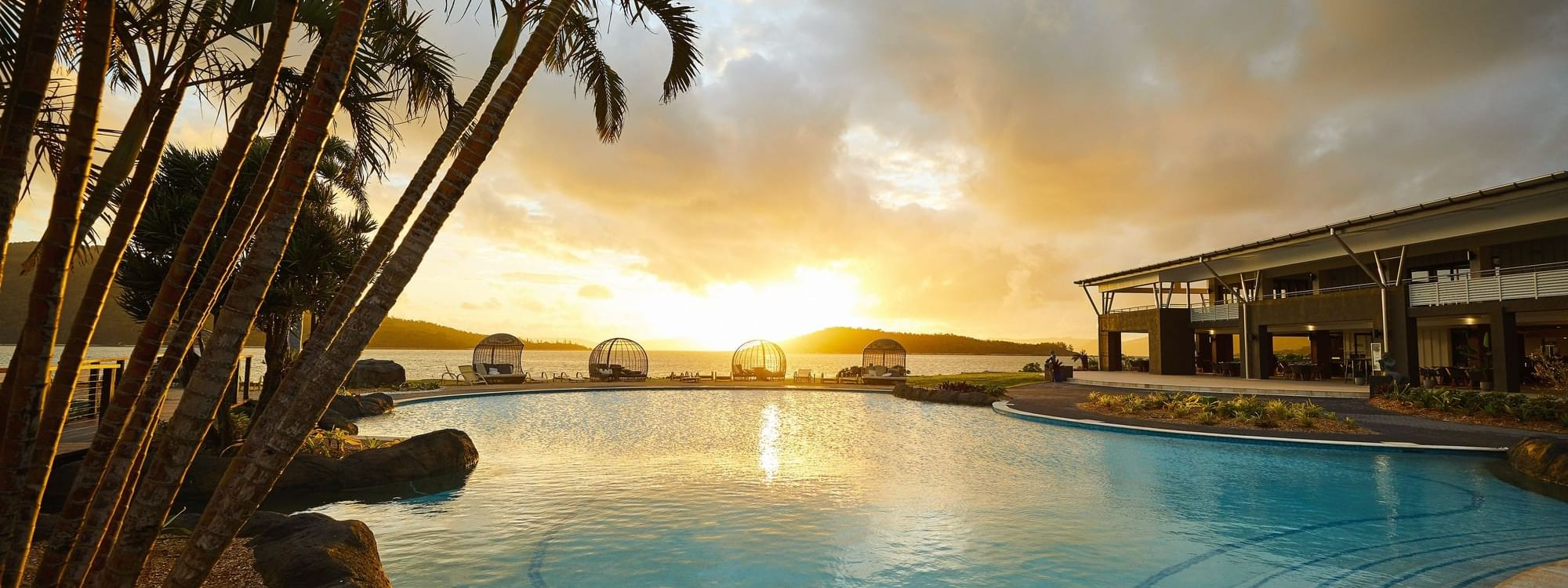Swimming Pool and palm tree at sunset at Daydream Island Resort