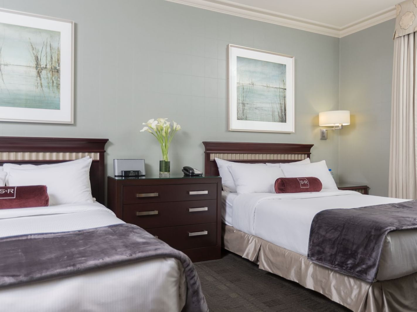 two double beds in hotel room with wall artwork