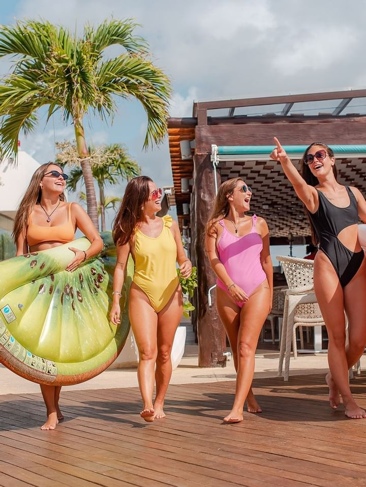 Four girls walking on the pool deck at The Reef 28