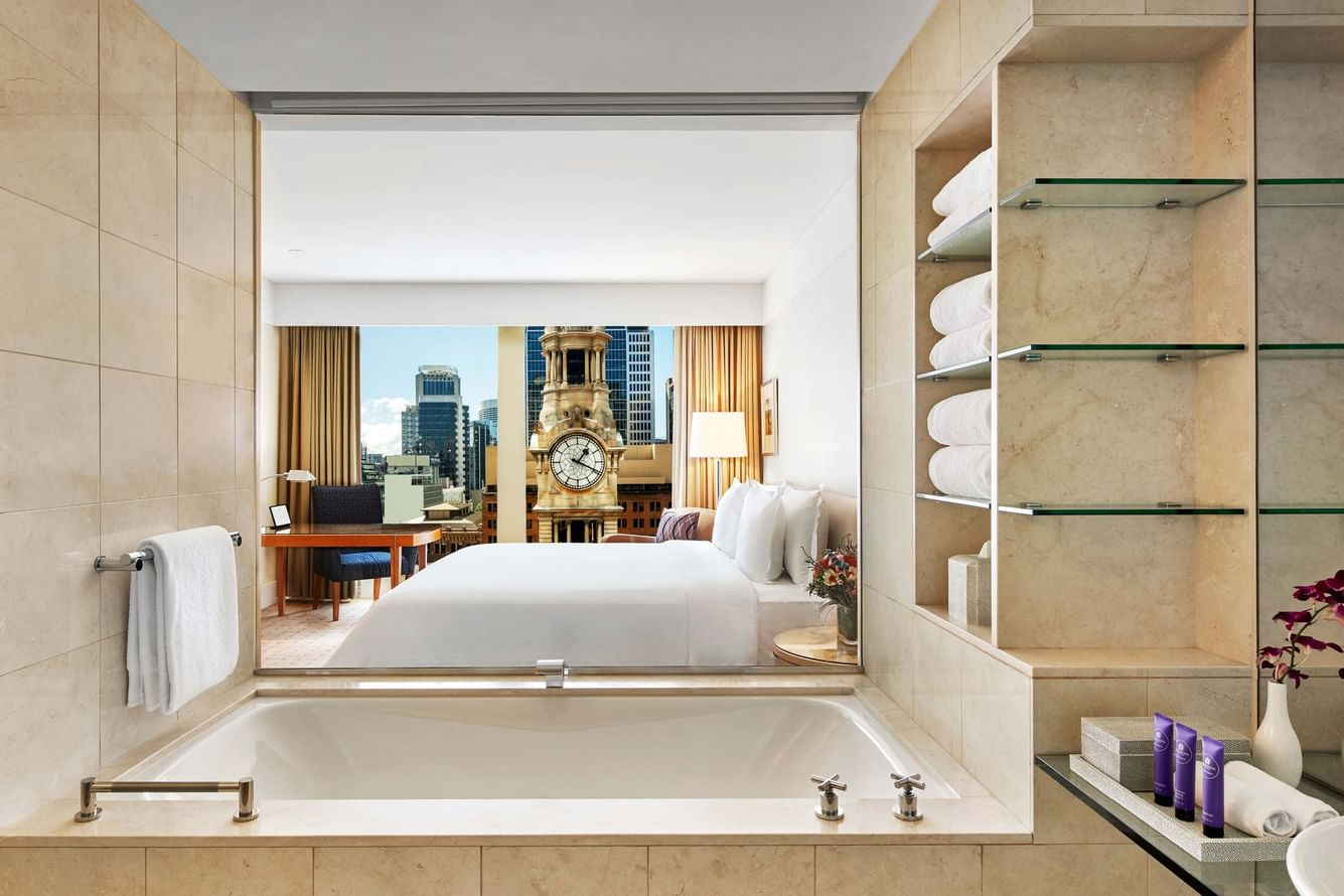 A bathroom with a bathtub connecting to the bedroom