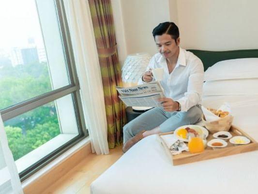 man sitting on bed enjoying food on tray reading newspaper