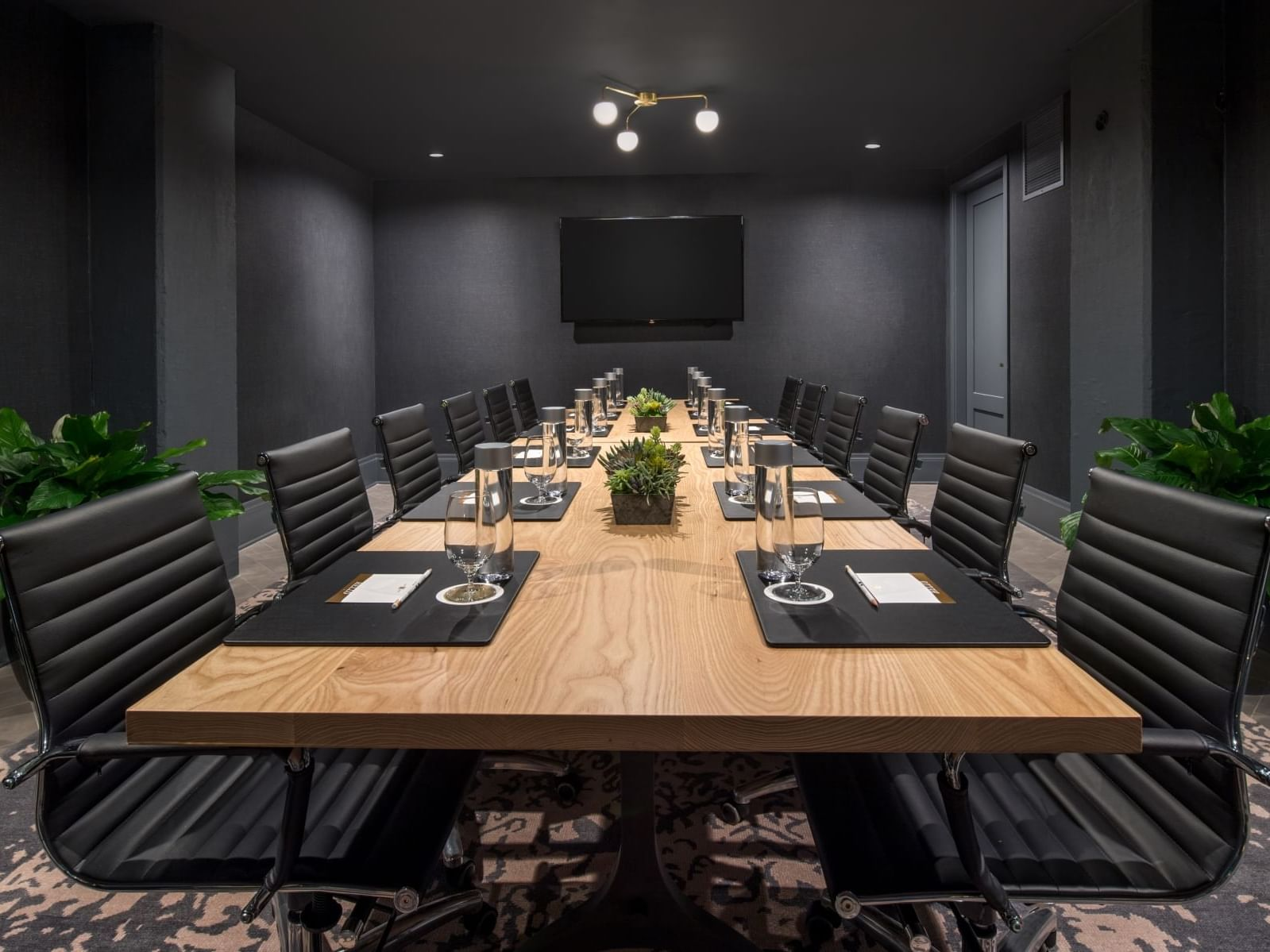 conference room with table, chairs and television mounted on wall