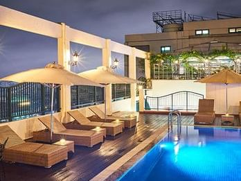 hotel swimming pool with day beds at night