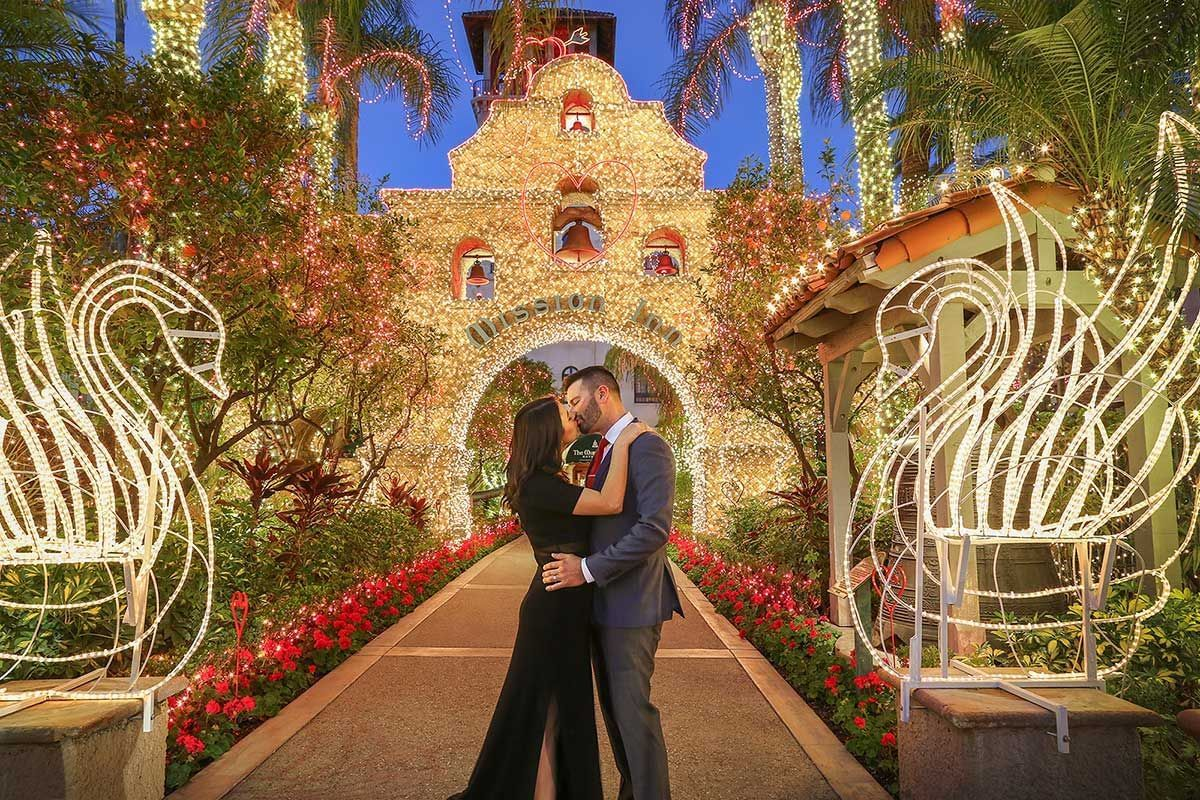 couple kissing at Mission Inn entrance decorated with christmas