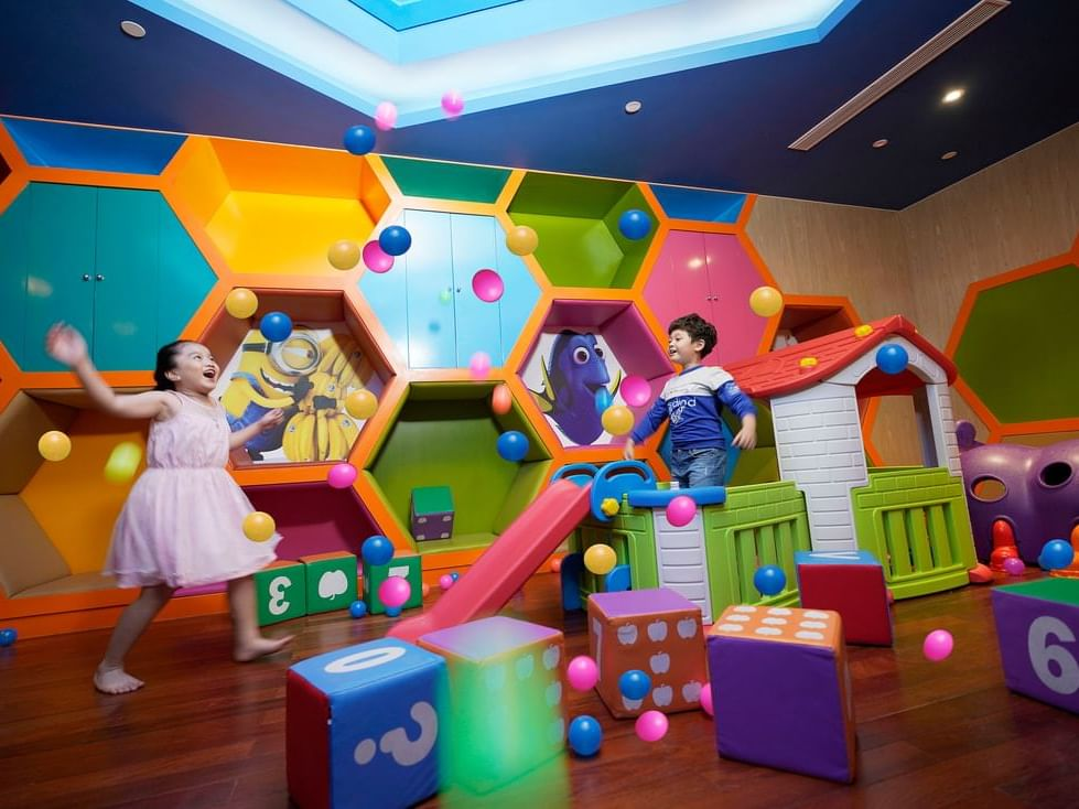 2 children playing in colourful indoor playground