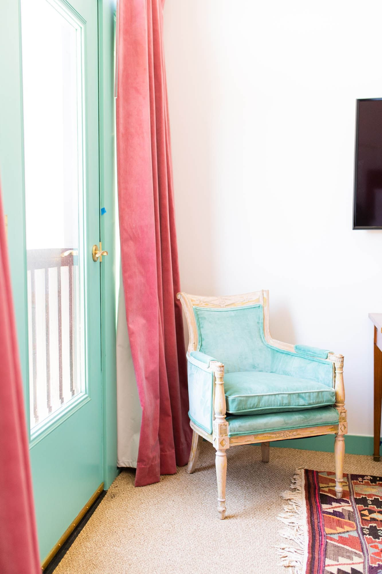 blue door and blue chair in white room with pink curtains