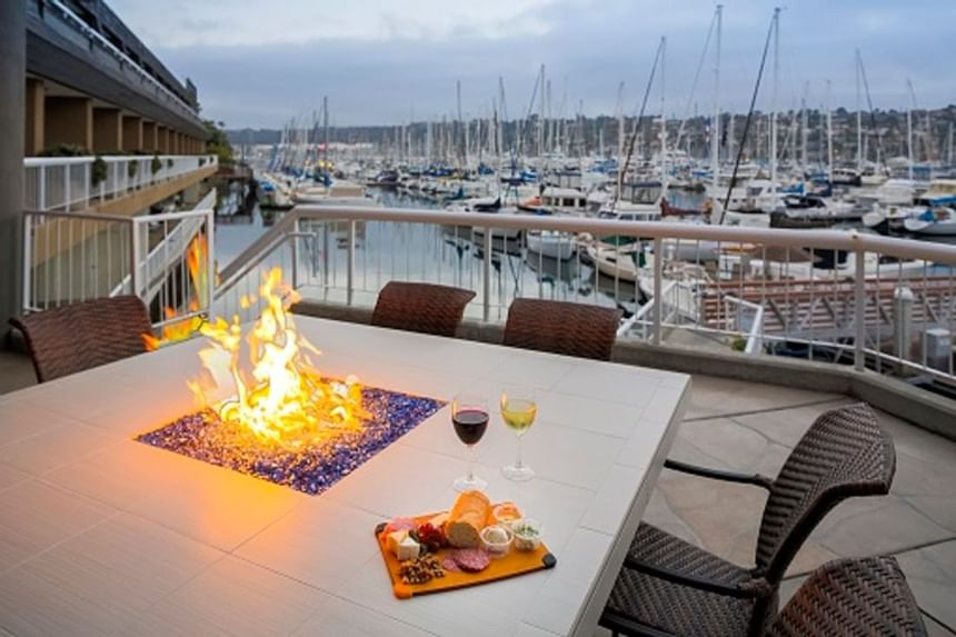 Wine & cheese platter on a fire table outside at Bay Club Hotel