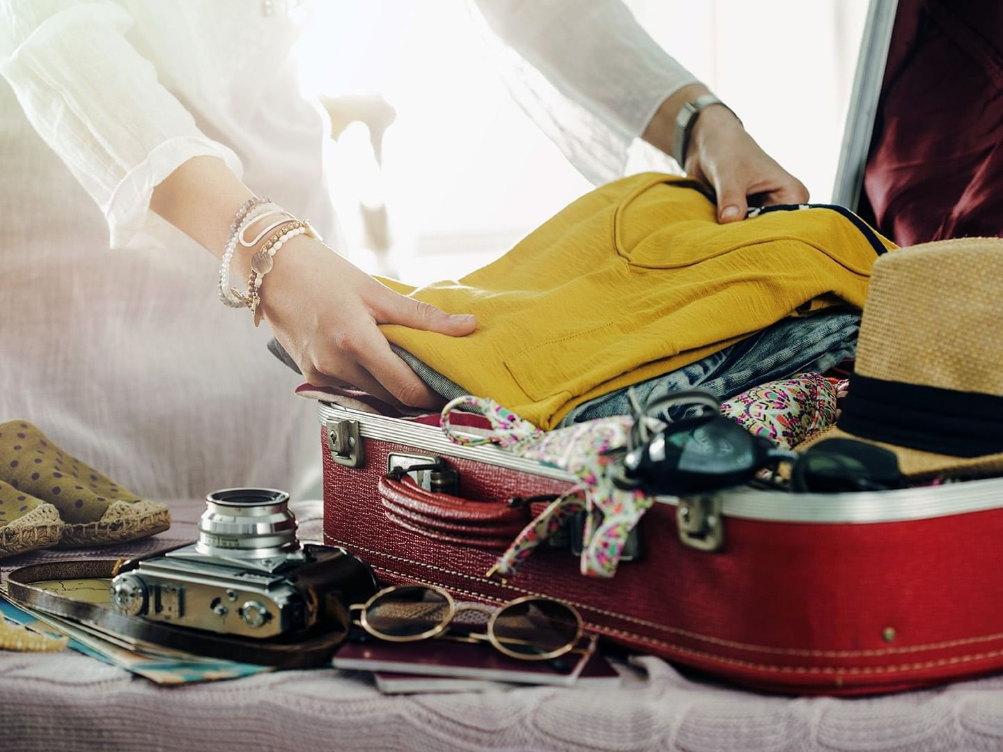 A closeup picture of a woman packing a suitcase