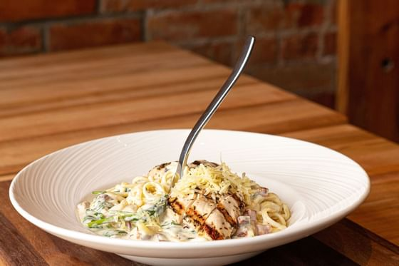 a fork stands upright in a bowl of chicken alfredo pasta